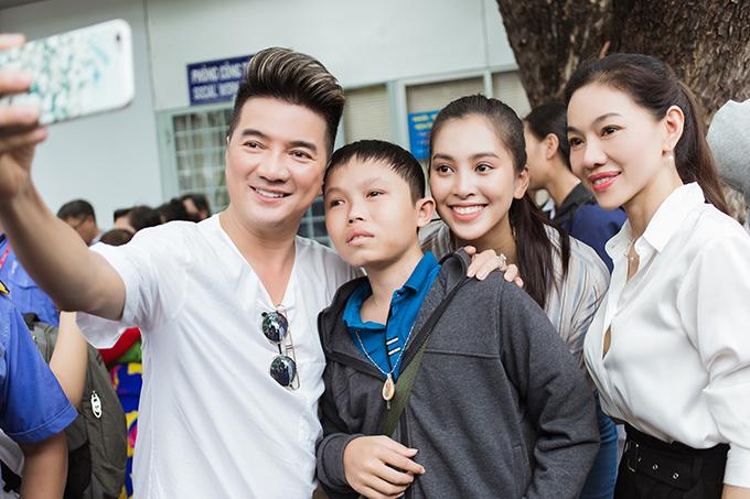 Ca sĩ Đàm Vĩnh Hưng cầm điện thoại, cùng Tiểu Vychụp hình với một em nhỏ.