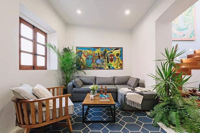 Phòng khách trải thảm hoa văn hình học, tạo bối cảnh cho phần còn lại của ngôi nhà. Cảm giác sống động, giàu sức sống đến từ những bức tranh màu sắc trên tường.