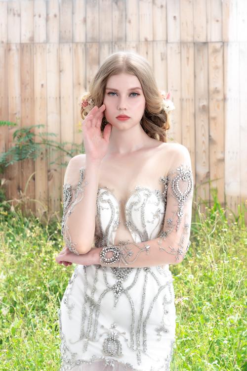 Bộ đầm cũng áp dụng xu hướng cổ illusion (cổ 2 trong 1) với cổ tàng hình làm từ voan mỏng, tôn vòng ngực quyến rũ của tân nương. Các chi tiết đính kết như ngọc, đá quý trên thân váygiúp hoàn thiện vẻ đẹp nữ tính, kiêu sa của nàng dâu.