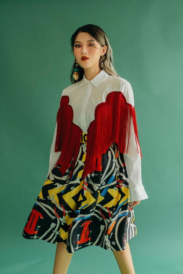 Mẫu sơ mi trắng phom dáng basic trở nên ấn tượng hơn với cách trang trí vạt tua rua tông đỏ. Trang phục đi kèm là chân váy in họa tiết.