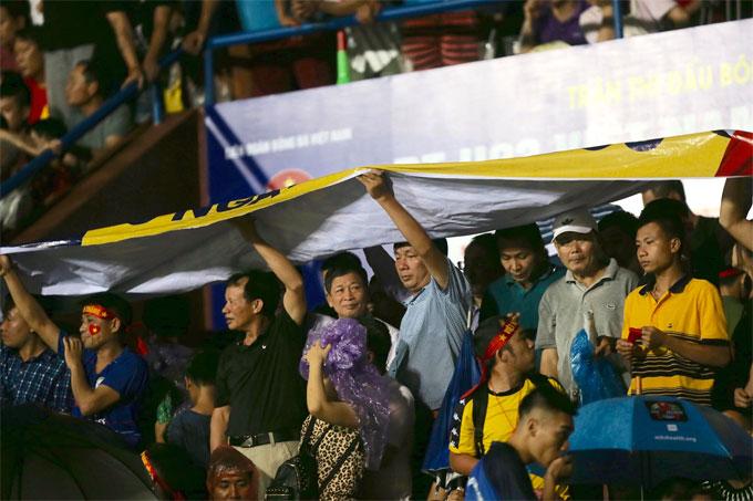 Fan tận dụng mọi vị trí để tránh mưa, tiếp tục chờ đợi quyết định của ban tổ chức có cho trận đấu bắt đầu hiệp hai hay không.