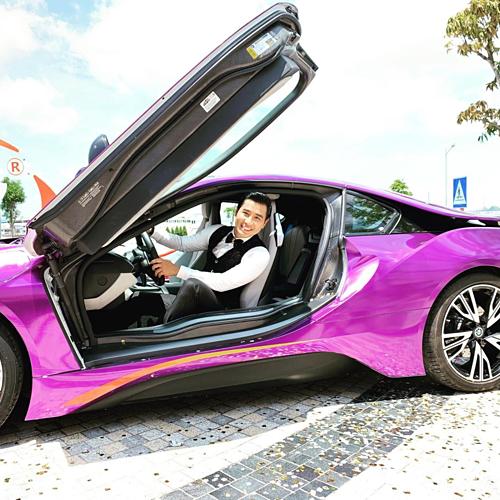 MC Nguyên Khang cố tạo dáng sống ảo với siêu xe dù trời nắng nóng.