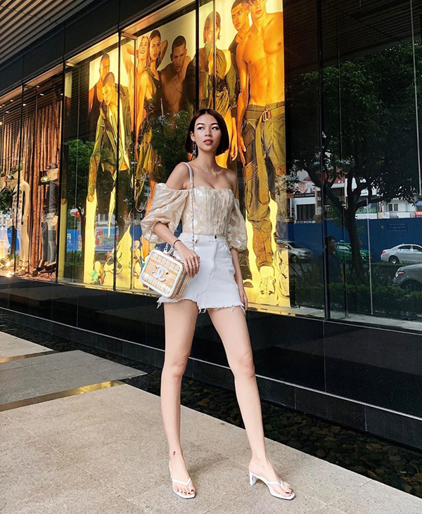 Áo trễ vai đi kèm tay bồng được Phí Phương Anh mix cùng short jeans rách kiểu lưng cao. Scandal và túi xách Chanel hợp màu cũng được sử dụng để hoàn thiện set đồ.