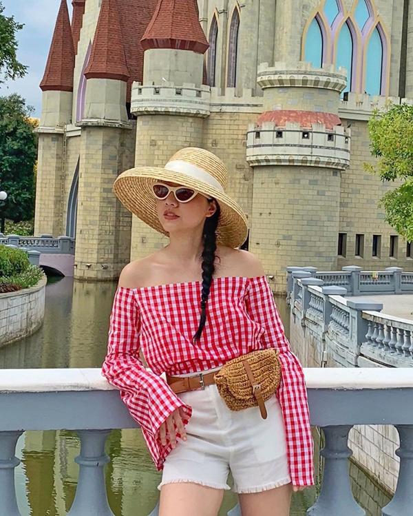 Băng Di trẻ trung và sexy khi đi du lịch với set đồ gồm áo ca rô, short jeans rách, mũ rộng vành và belt bag trên chất liệu thân thiện với môi trường.