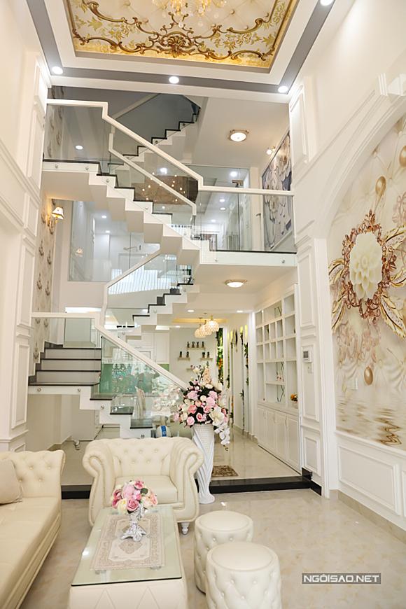 Gam màu chủ đạo anh sử dụng cho ngôi nhà mới là trắng và vàng đồng. Tầng trệt là phòng khách và khu vực bếp thiết kế đơn giản, hiện đại.