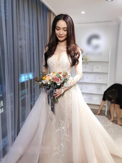 Váy cưới được may bằng vải ren Pháp, có họa tiết hoa trải thành dải dây leo mềm mại. NTK Phương Linh điểm vài hạt pha lê, tạo hiệu ứng bắt sáng, gợi liên tưởng đến những giọt sương buổi sớm mai đọng trên kẽ lá.