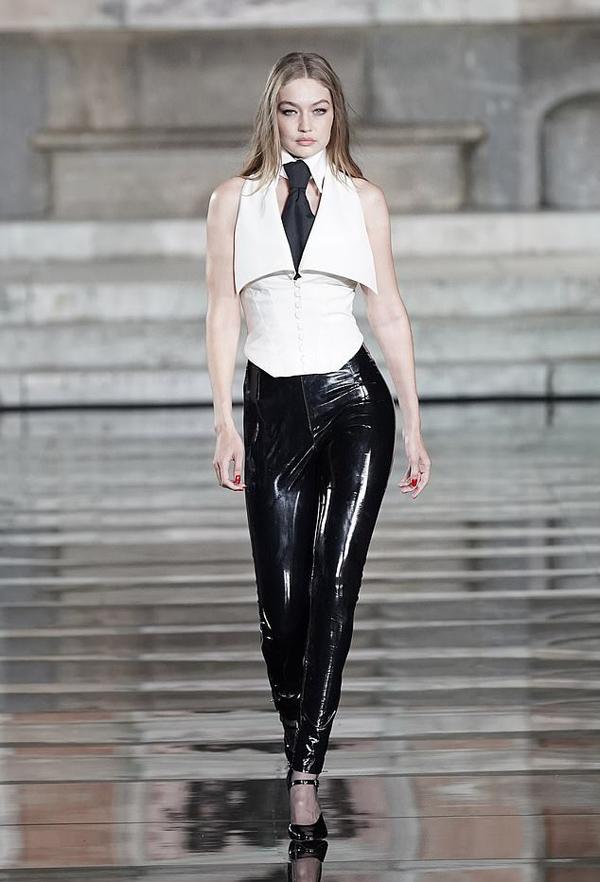 Show thời trang còn có sự góp mặt của chân dài đình đám Gigi Hadid. Cô khoe đường cong với áo bó eo và quần da bóng.