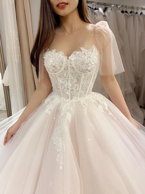Những dải hoa ren dây leo thả rơi từ từ ngực váy qua ngang eo càng tôn lên nét mềm mại, thanh tân của nàng dâu.