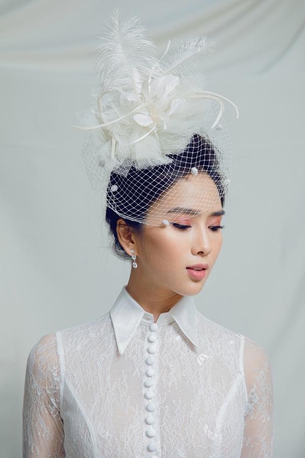 Nữ diễn viên búi tóc cao kết hợp khuyên tai đính đá và kiểu trang điểm cổ điển để hoàn thiện phong cách.