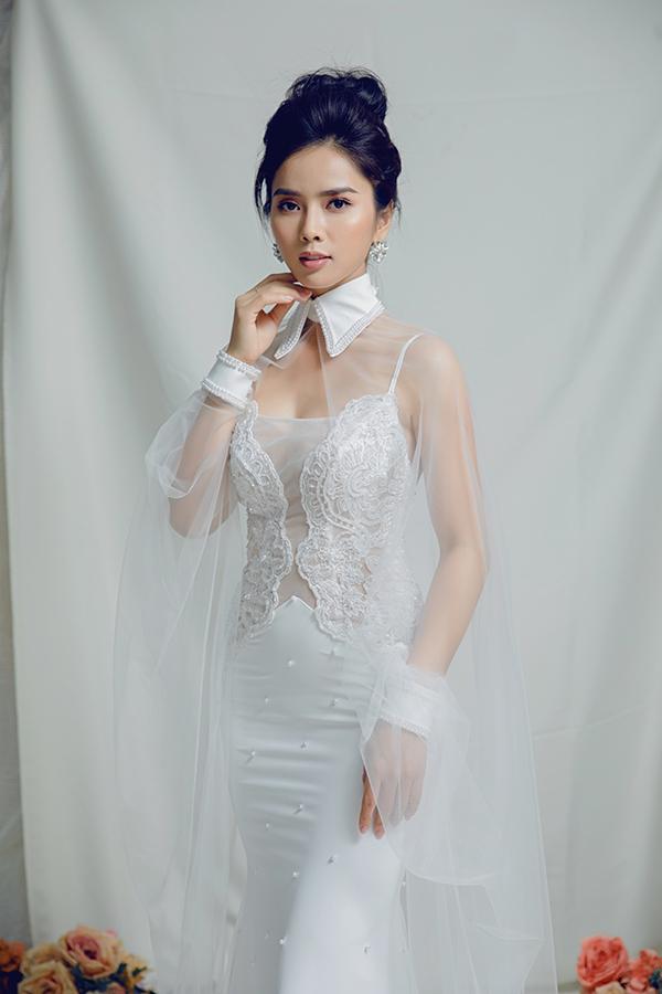 Áo cape chất liệu voan mỏng lấy cảm hứng từ sơ mi cổ đức làm tôn lên bờ vai gợi cảm của Bella Mai.