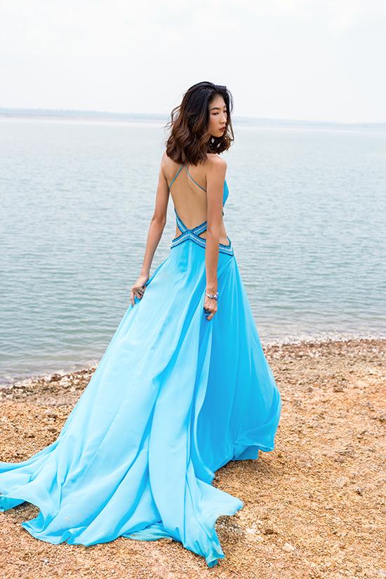Trên chất liệu vải đơn sắc, nhà thiết kế áp dụng các kỹ thuật đính kết để tạo nên hoạ tiết độc đáo cho váy khoe lưng trần.