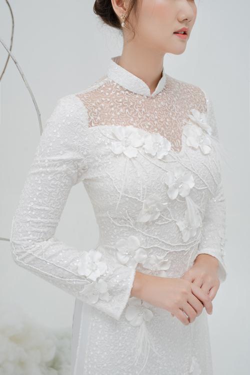 Điểm xuyết cho vẻ thanh tú của cô dâu là những đóa hoa 3D dọc thân trên và hai bên tay áo.