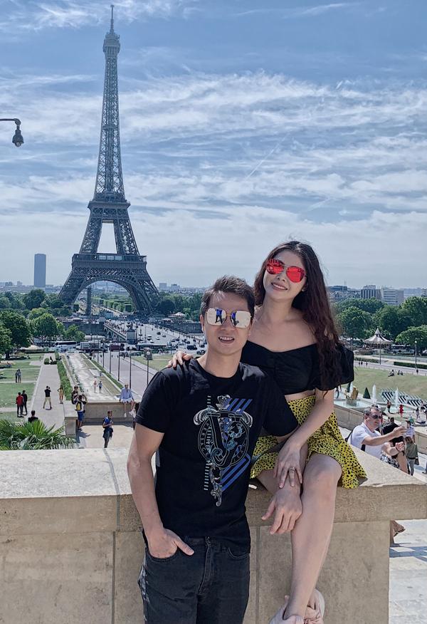 Nam ca sĩ và vợ mặc ton-sur-ton đen chụp ảnh kỷ niệm với tháp Eiffel - biểu tượng của Paris.
