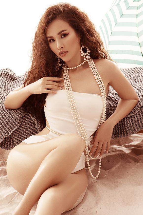 Thanh Trang hoàn thiện phong cách gợi cảm,sang trọng khi diện bikini màu trắng bằng cách phối thêm dây chuyền và khuyên tai ngọc trai to bản.