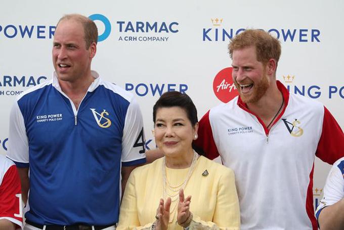 Harry ôm lưng, chúc mừng anh trai chiến thắng trong trận polo khi chụp ảnh trên bục nhận cúp cùng vợ của cố tỷ phú Vichai hôm 10/7. Ảnh: PA.