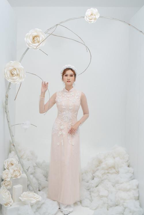 4. Áo dài hồng pastel họa tiết hoa nổiMẫu áo được thêu đính họa tiết hoa nổi, làm toát lên vẻ thanh tú của tân nương. Mẫu áo có sự học hỏi từ thời trang váy cưới với nhiều lớp vải, chi tiết tay từ voan xuyên thấu.