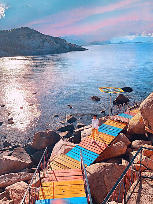 Màu sắc con đường bắt mắt, nằm ngay sát biển khiến du khách ngỡ như lạc chân tới đảo Jeju (Hàn Quốc). Bạn có thể căn được nhiều góc máy như chụp từ trên cao để lấy toàn bộ con đường, rặng đá và biển phía xa; hoặc chụp ngang tầm mắt để vừa lấy con đường, vừa lấy được mặt biển và bầu trời. Ảnh: Hợi Heo Bình Hưng