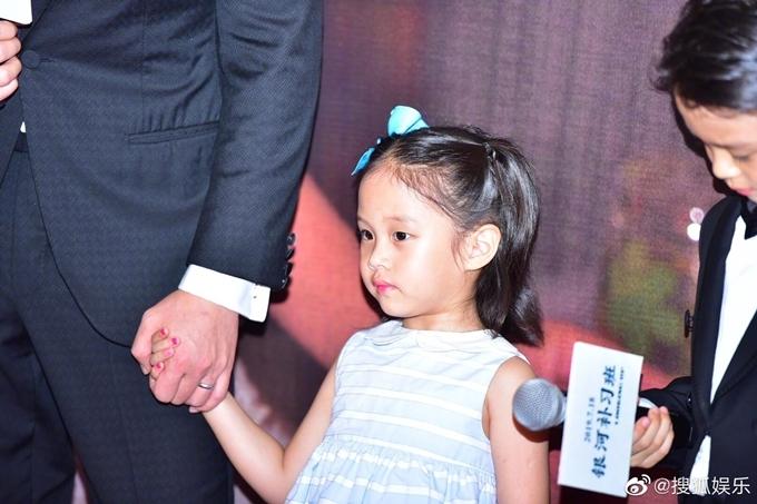 Cô bé Tiểu Hoa còn bình tĩnh hơn cả anh trai khi đứng trước rừng máy ảnh.