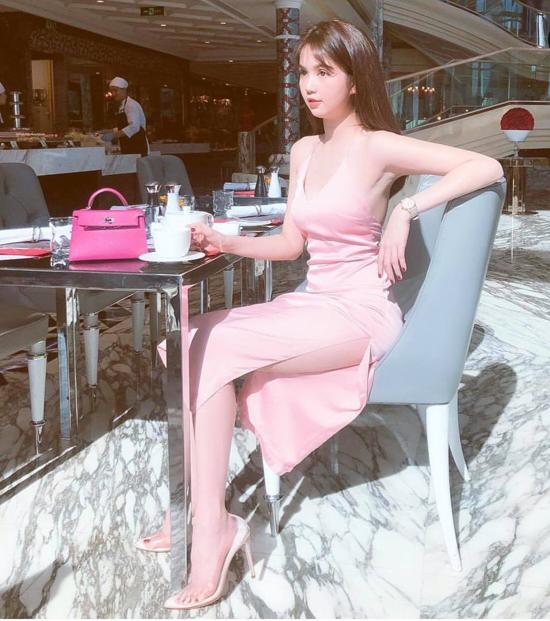 Túi Hermes sắc hồng cánh sen được Ngọc Trinh sử dụng cùng váy hồng phấn nhẹ nhàng và giày nhựa trong đế trắng.