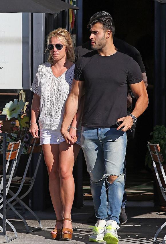 Chàng người mẫu Sam Asghari nắm chặt tay Britney khi rời quán ăn.