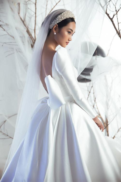 Phía sau lưng váy là khoảng hở giúp cô dâu khoe tấm lưng thon và nơ to bản để tạo điểm nhấn trong thiết kế.