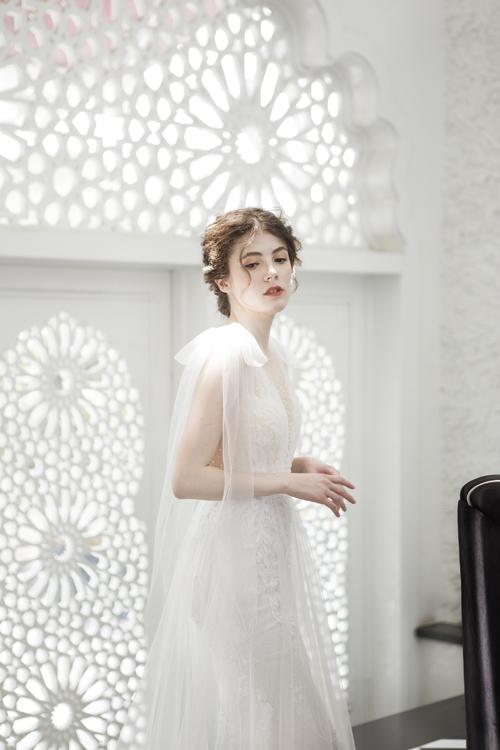 Để từng cái nhấc tay của cô dâu trở nên uyển chuyển, cầu vai được điểm nơ có tà dài.