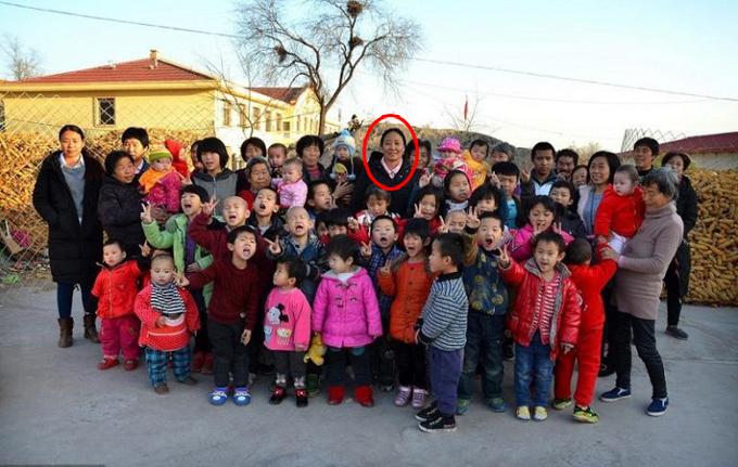 Bà Li (khoanh đỏ) chụp ảnh cùng các nhân viên và trẻ mồ côi ở Ngôi làng tình thương tại thành phố Ngô Tối, tỉnh Hà Bắc, Trung Quốc. Ảnh: Weibo.