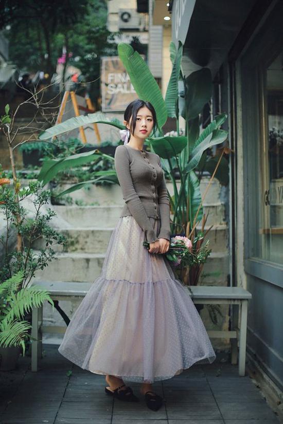 Váy vải tuyn được tạo khối bồng bênh để mang tới nét xinh xắn cho bạn gái. Vào những ngày mưa, chọn thêm cardigan hay áo khoác dệt kim sẽ mang đến set đồ hoàn hảo.