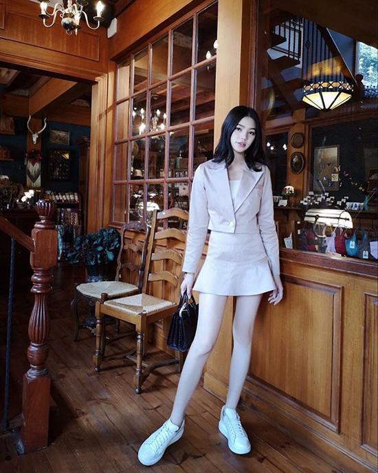 Jolie Nguyễn tôn chân thon bằng váy chữ A dáng ngắn đi cùng vest tiệp màu.