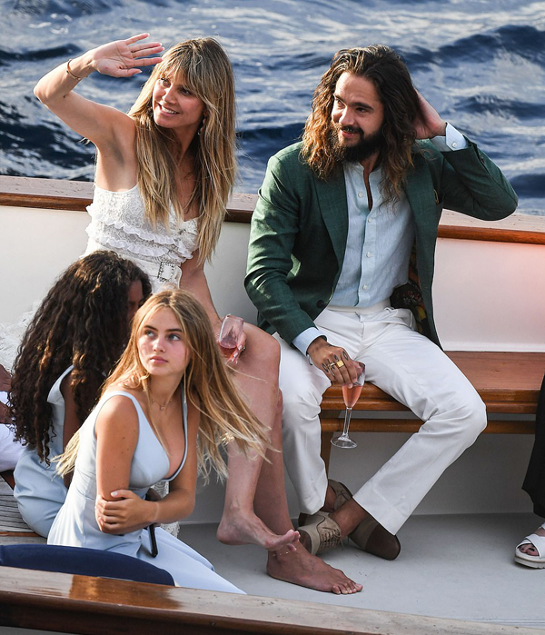 Heidi Klum ngồi bên Tom Kaulitz trên chiếc thuyền đưa họ từ đất liền ra đảo Capri, Italy. Cả hai đều rạng ngời hạnh phúc trước ngày cưới. 4 người con riêng của Heidi là Leni 14 tuổi (tóc vàng bên trái), Henry 12 tuổi, Johan 11 tuổi và Lou 8 tuổi ngồi bên cạnh.