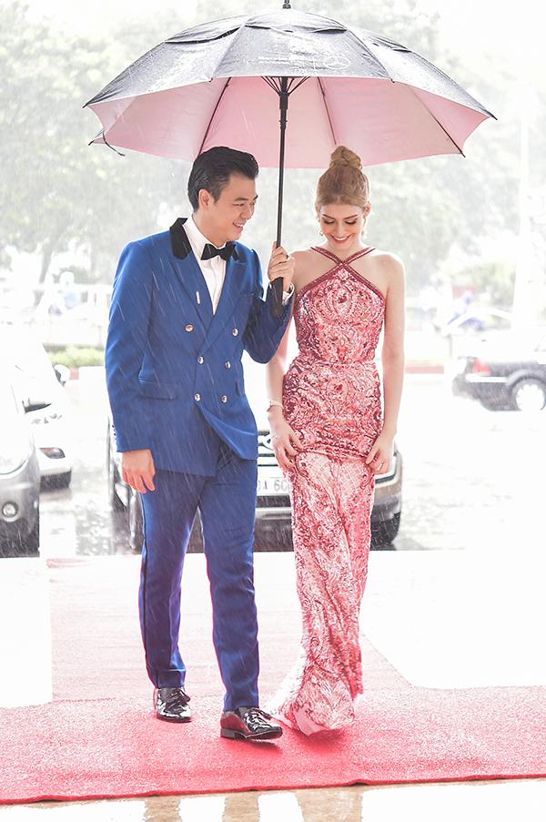 An Tây mặc váy đuôi cá bó sát, gặp khó khăn khi di chuyển nên MC Tuấn Tú đã cầm ô ra tận xe đón cô trong cơn mưa xối cả.