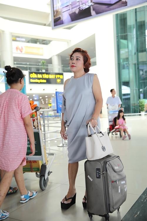 Nữ ca sĩmặc chiếc váy màu xanh, mang hành lý đơn giảntrong chuyến ra Hà Nội sau thời gian ở ẩn.