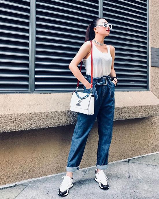 Một chút cá tính và đan xen sự sexy là những gì Trà Ngọc Hằng có được khi mix đồ với áo thun ba lỗ, quần jeans lưng cao, giày sneaker hài hòa cùng túi hiệu Louis Vuitton.