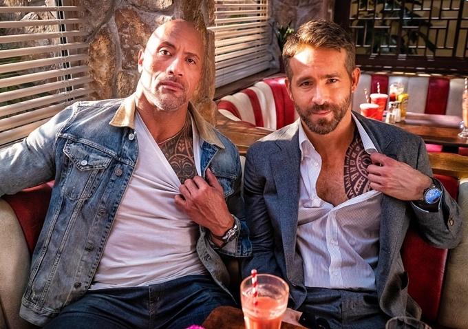 Ngôi sao Deadpool Ryan Reynolds (phải) và tài tử cơ bắp Dwayne Johnson cùng khoe hình xăm trên phim trường.