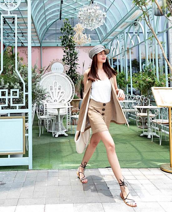 Áo sát nách được sử dụng cùng long vest và chân váy đồng điệu về màu sắc và chất liệu. Bộ cảnh tôn chân thon dài và xây dựng hình ảnh gợi cảm cho người mặc.