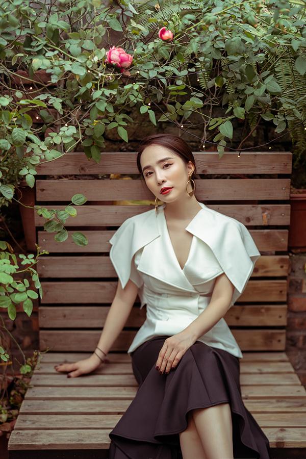 Kết hợp áo vest cách điệu màu trắng giúp cho chiếc váy đen dáng lửng bớt già dặn. Để giữ được sự tươi trẻ khi mặc đồ công sở,người đẹp kết hợp thêm khuyên tai to bản.