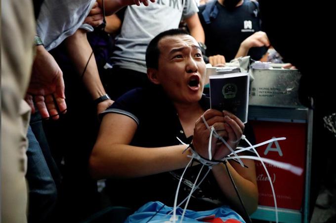 Phóng viên Fu Guohao bị người biểu tình trói ở sân bay quốc tế Hong Kong hôm 13/8. Ảnh: Reuters.