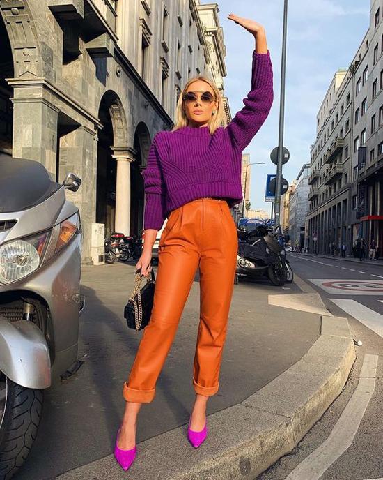 Set đồ cho các nàng yêu thích trào lưu mới với lối mix-match tông màu chóe gồm quần da cam và áo len tông tím đậm.