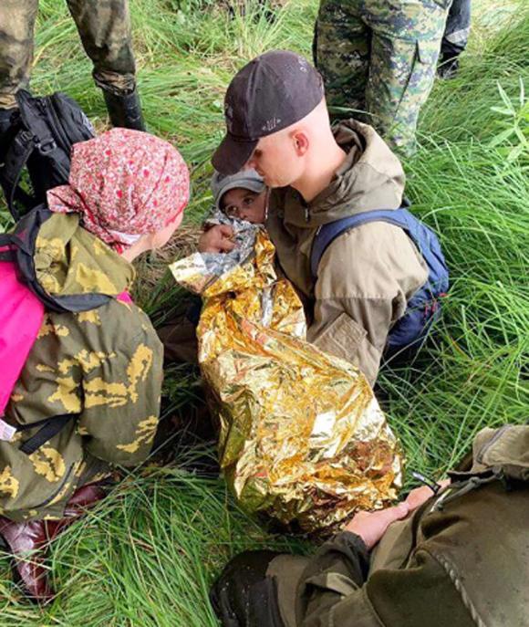 Nhân viên cứu hộ ôm lấy Kolya sau khi tìm thấy cậu bé hôm 14/8. Ảnh: East2west News.