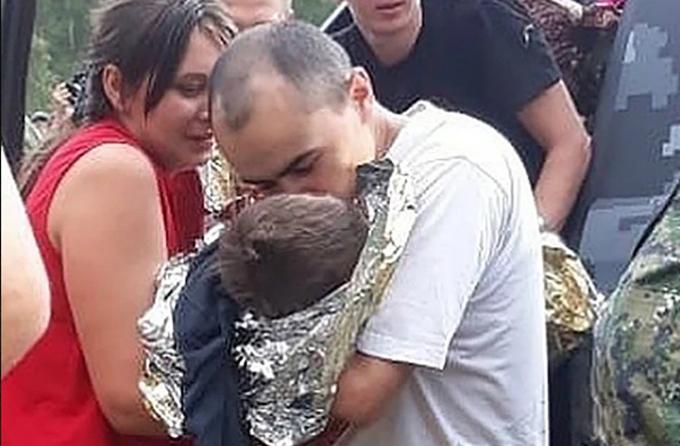 Bố mẹ Kolya ôm lấy con trai sau khi cứu được con từ trong rừng ra. Ảnh: East2west News.