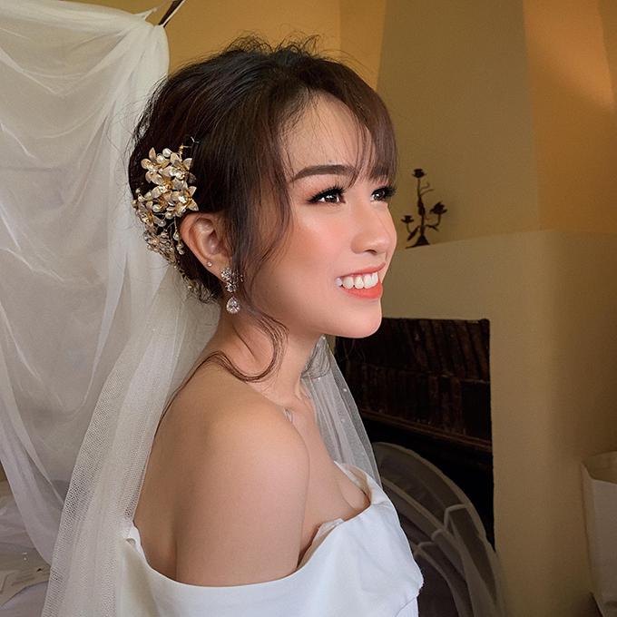Điểm khác biệt ở layout này so với ngày chụp đầu tiên nằm ở màu son, đôi mắt. Ty Lê pha thêm tông đỏ tươi cho lòng môi để tạo sự nổi bật cho cô dâu khi diện váy cưới.