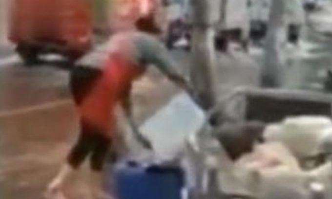 Nữ nhân viên của Busan Stove múc nước từ vũng nước đổ vào chậu lớn để rửa bát. Ảnh: Weibo.