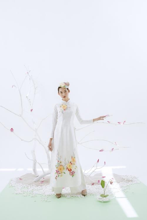 Áo dài nữ sắc trắng được thêu họa tiết đóa mẫu đơn nơi khuôn ngực, chân tà, tạo điểm nhấn.