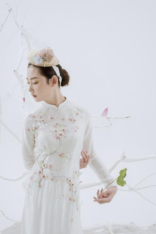 Bộ áo điểm họa tiết hoa nhí thêu nổi. Phần cổ áo được đính hạt ngọc, tạo hiệu ứng bắt sáng.