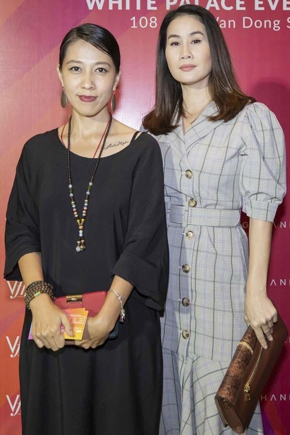 Cựu người mẫu Thân Thuý Hà (phải) sải bước trên thảm đỏ cùng vợ của Phạm Anh Khoa.
