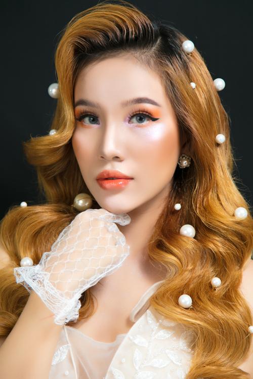 Layout đầu tiên mà Thiên Tuấn lựa chọn có tông cam sáng chủ đạo, dành cho cô dâu có nước da trắng ngần. Điểm nhấn ở gương mặt là đôi mắt kẻ eyeliner mắt mèo, phấnhồng nhạt ở phần đầu mắt và phấn cam ở cuối đuôi. Môi và má đều phủ tông cam đất, tạo vẻ khỏe khoắn cho diện mạo. Kiểu tóc dành cho layout này là tóc xoăn buông xõa, đính hạt ngọc trai rải rác từ đỉnh đầu tới cuối đuôi tóc, tạo nên diện mạo ấn tượng.