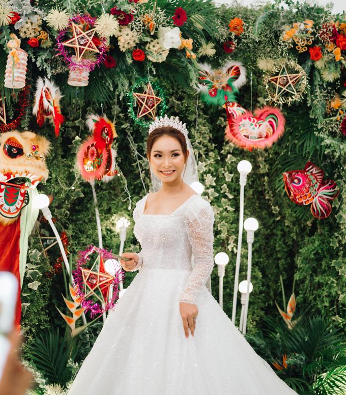 Cô dâu diện váy cưới dáng xòe, cổ vuông,được đính kết hạt đá lấp lánh dọc thân.