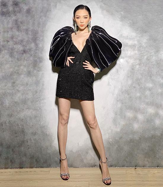 Ca sĩ Tóc Tiên tôn chiều cao với váy ngắn sexy. Mẫu đầm đen phối vải tweed, vải bóng còn được trang trí phần vai phồng bắt mắt.