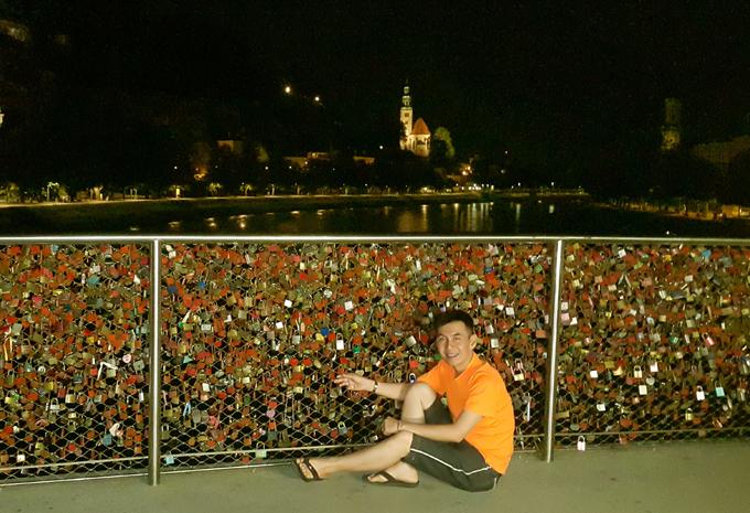 [Caption]Hình 24: Buổi tối anh tự mình lang thang khám phá cầu tình yêu tại quảng trường Mozart, thành phố Salzburg.