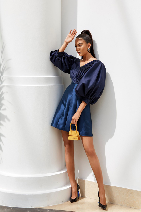 Mẫu túi tí hon của thương hiệu nổi tiếng không chỉ được sử dụng để mix đồ street style, nhiều sao Việt còn dùng nó để tăng sức hút cho set đồ đi tiệc. Mâu Thủy chọn túi tông vàng mù tạt phối cùng váy tay bồng.